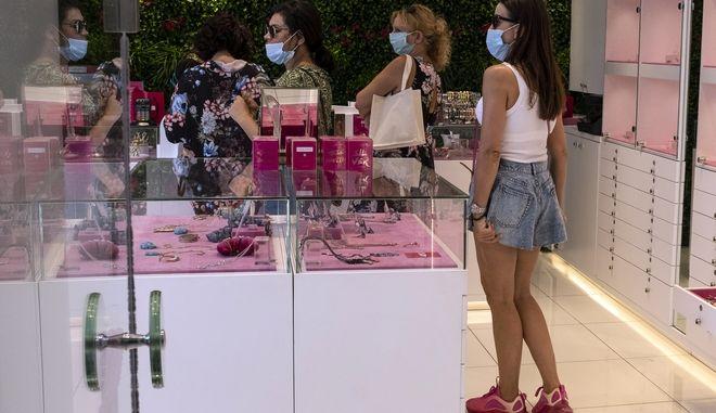 Γυναίκες με μάσκες κάνουν τα ψώνια τους στη Γλυφάδα