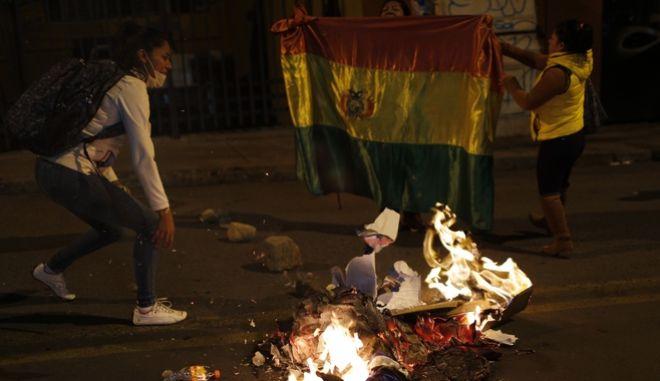 Υποστηρικτές του Μέσα καίνε πανό του κυβερνώντος κόμματος.