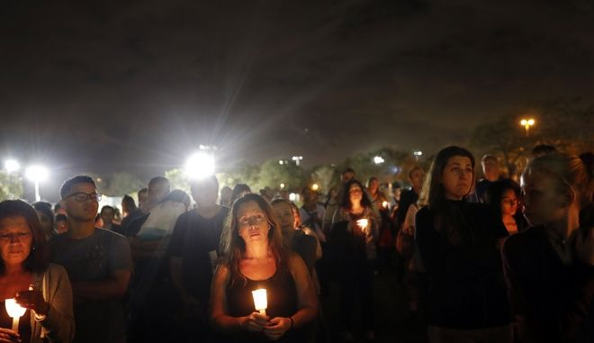 People participate in a candlelight vigil in memory of the 17 students and faculty who were killed in the Wednesday mass shooting at Marjory Stoneman Douglas High School in Parkland, Fla., Monday, Feb. 19, 2018. Nikolas Cruz, a former student, was charged with 17 counts of premeditated murder on Thursday. (AP Photo/Gerald Herbert)