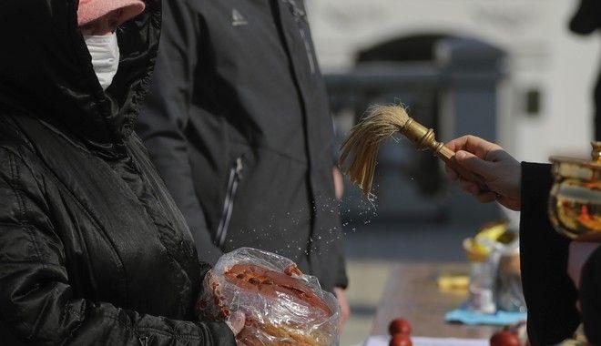 Σε εκκλησία του Μινσκ, οι πιστοί παίρνουν την ευλογία του ιερέα, σε κέικ και πασχαλινά αυγά