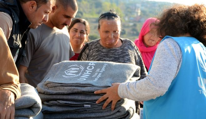 Community leader Omar Idu works with interpreter, Lisa Gabrilidis and UNHCR Protection Officer, Erin Hampton to distribute thermal blankets to residents of Faneromeni camp.  The amount of blankets coincides with the size of each family. ; As winter approaches, UNHCR prepares camps for winterization with the distribution of non-food items like thermal blankets.  Faneromeni is a facility rented by UNHCR to accommodate Yazidis refugees and asylum-seekers.  The blankets are funded by the European Union's EU Humanitarian Aid and Civil Protection department (ECHO).