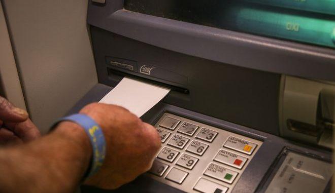 Άνδρας παίρνει απόδειξη από ATM, Αρχείο