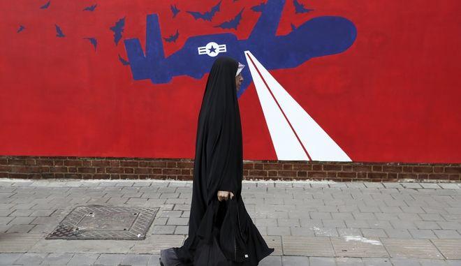 Γυναίκα περπατά μπροστά από γκράφιτι στο Ιράν