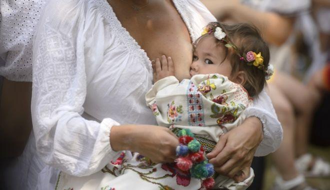 Μία γυναίκα θηλάζει τη 18 μηνών κόρη της, Ρουμανία, 6/8/2016