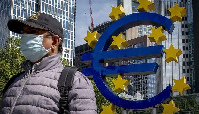Άνδρας που φοράει μάσκα έξω από την Ευρωπαϊκή Κεντρική Τράπεζα