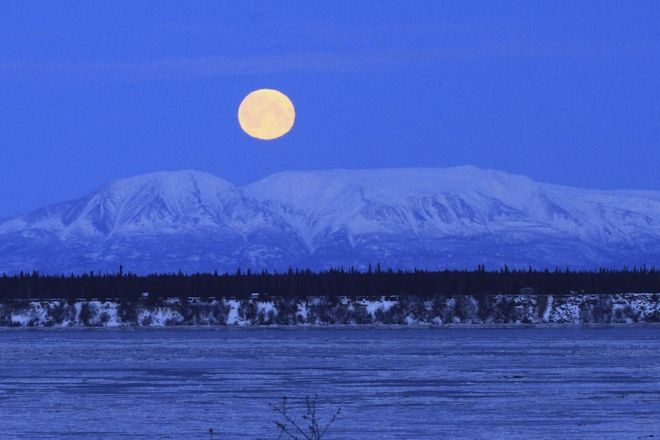 The moon sets over Mount Susitna, known locally as Sleeping Lady, across Cook Inlet on Wednesday, Jan. 31, in Anchorage, Alaska. (AP Photo/Dan Joling)