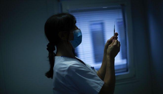 Νοσοκόμα στο Βέλγιο ετοιμάζεται να κάνει εμβόλιο κατά του κορονοϊού σε ασθενή