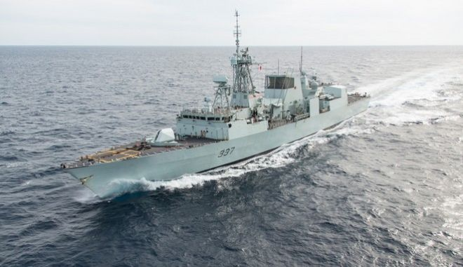 English Descriptive:  Her Majesty's Canadian Ship Fredericton hoists its Battle Ensign upon completion of an Anti-Ship Missile Defence Exercise in an operating area outside of Norfolk, Virginia, on November 6, 2014. This exercise was part of the Halifax-class frigate's ongoing modernization process.   Credit: Photo: Lt(N) Jennifer Fidler, Royal Canadian Navy Public Affairs   IS2013-7200-0X