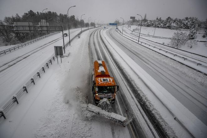 A plough clears snow from a highway during a heavy snowfall in Rivas Vaciamadrid, Spain, Saturday, Jan. 9, 2021. An unusual and persistent blizzard has blanketed large parts of Spain with snow, freezing traffic and leaving thousands trapped in cars or in train stations and airports that had suspended all services as the snow kept falling on Saturday. The capital, Madrid, and other parts of central Spain activated for the first time its red weather alert, its highest, and called in the military to rescue people from cars vehicles trapped in everything from small roads to the city's major thoroughfares. (AP Photo/Manu Fernandez)