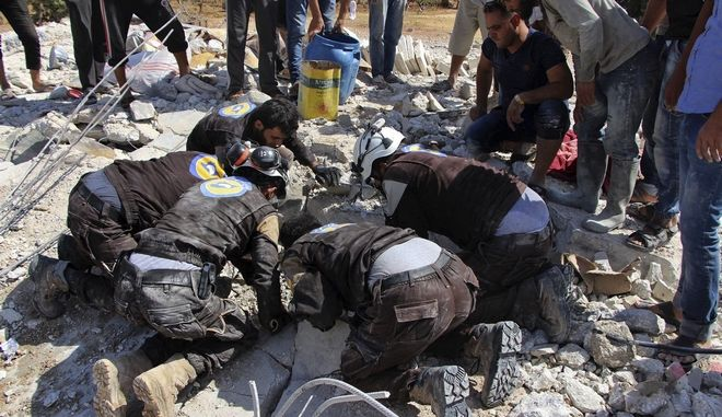 This photo provided by the Syrian Civil Defense White Helmets, which has been authenticated based on its contents and other AP reporting, shows civil defense workers searching in the rubble after airstrikes hit in Khan Sheikhoun, in the northern province of Idlib, Syria, Sunday, Sept, 24, 2017. A Syrian war monitoring group says airstrikes have targeted rural Aleppo for the first time in months since a cease-fire took hold in the province. (Syrian Civil Defense White Helmets via AP)