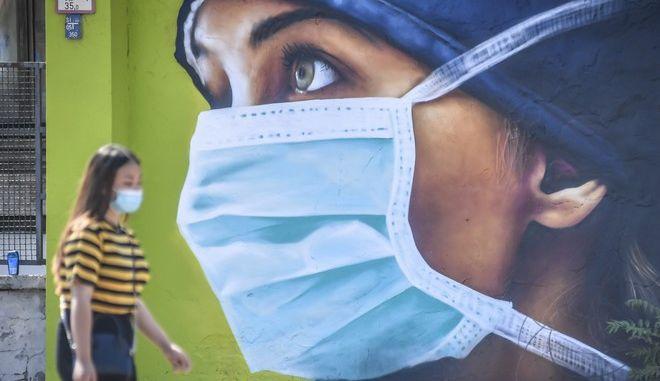 Γυναίκα φοράει μάσκα στην Ιταλία