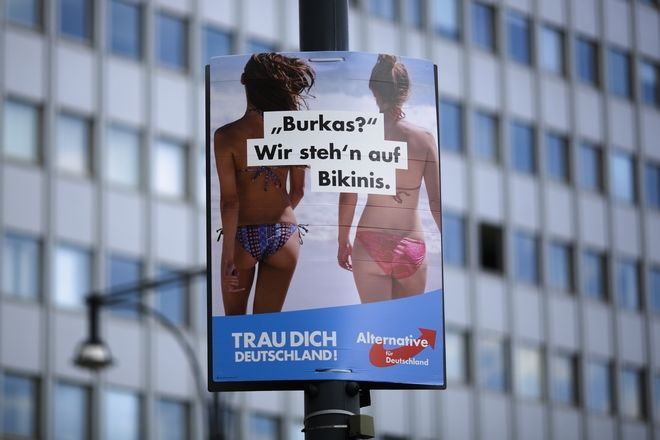 """An election campaign poster of the German anti-immigrant party AfD, Alternative for Germany, reading """"Burkas? We like bikinis."""" is displayed in central Berlin, Germany, Sunday, Aug. 13, 2017. General national election will be held in Germany on Sept. 24, 2017. The sentence at the bottom reads: 'Trust yourself Germany'. (AP Photo/Markus Schreiber)"""