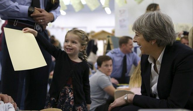 Britain's Prime Minister Theresa May smiles as a child holds a piece of paper at a kindergarten school during her visit to RAF Akrotiri, one of two military bases Britain maintains on the east Mediterranean island of Cyprus, on Friday, Dec. 22, 2017. May has praised military personnel at a U.K. air base on Cyprus for helping to beat back the Islamic State group with more than 1,600 air strikes in Iraq and Syria. (AP Photo/Petros Karadjias, Pool)