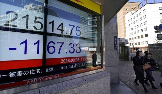 Άνθρωποι περπατούν μπροστά από πίνακα χρηματιστηριακών συναλλαγών