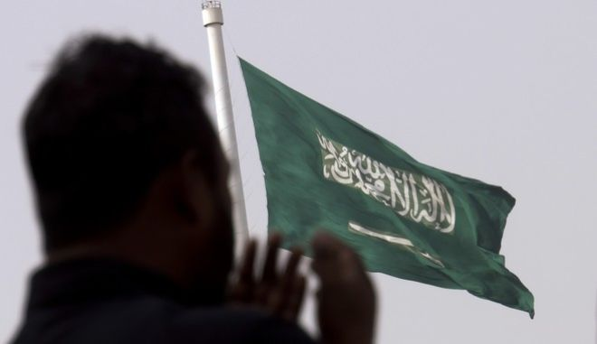 A man prays at an open air makeshift mosque in front of a giant Saudi Flag in Jiddah, Saudi Arabia, Wednesday, June 21, 2017. Saudi Arabia's King Salman on Wednesday appointed his 31-year-old son Mohammed bin Salman as crown prince. (AP Photo/Amr Nabil)