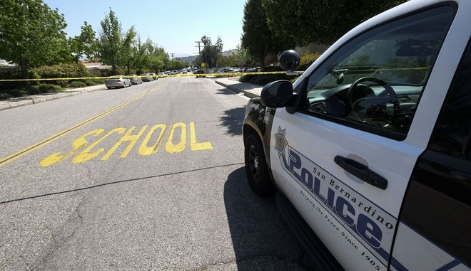 A police car is seen outside North Park School after a shooting ,Monday, April 10, 2017, in San Bernardino, Calif.. An apparent murder-suicide inside an elementary school classroom in San Bernardino left two adults dead, including a teacher, and two students wounded, police and school officials said. (AP Photo/Ringo H.W. Chiu)