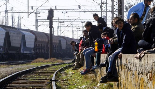 Refugees from Afghanistan sit beside railway tracks near a transit center for refugees at the Macedonian-Serbian border in the northern Macedonian village of Tabanovce, Monday, Feb. 22, 2016. More than 600 Afghan refugees were stranded since Saturday at the transit center while waiting for a permission to cross the border into Serbia. Serbia says the decision to block refugees from Afghanistan from passing through the so-called Balkan migrant corridor has been made by Austria and Slovenia. (AP Photo/Boris Grdanoski)
