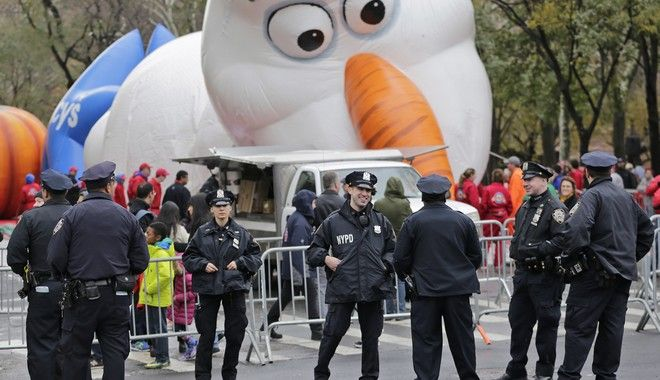 Police officers stand near the site where a large balloon of the character Olaf from