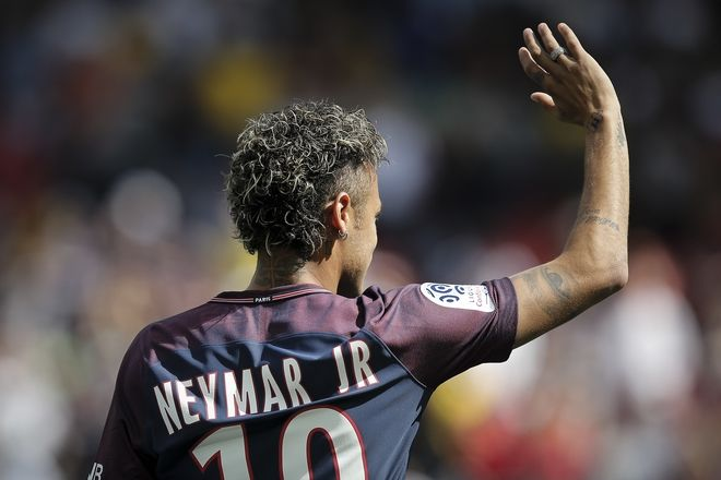 Brazilian soccer star Neymar waves to fans, at the Parc des Princes stadium in Paris, Saturday, Aug. 5, 2017, during his official presentation to fans ahead of Paris Saint-Germain's season opening match against Amiens. Paris Saint-Germain fans got their first chance to see Neymar inside the Parc des Princes but the world's most expensive player left the pitch after 24 minutes. Neymar cannot play as the club did not receive his international transfer certificate before Friday night's deadline despite his 222 million-euro ($262 million) move from Barcelona being completed the previous day. (AP Photo/Kamil Zihnioglu)