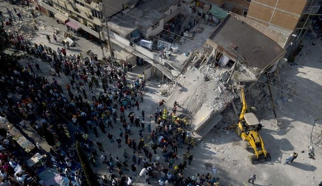 A bulldozer works on a collapsed building at the Ninos Heroes neighborhood in Mexico City, Tuesday Sept. 19, 2017. A magnitude 7.1 earthquake has stunned central Mexico, killing more than 100 people as buildings collapsed in plumes of dust. (AP Photo/Miguel Tovar)