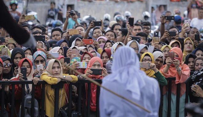 Φωτογραφία αρχείου, με μια γυναίκα στην Ινδονησία που τιμωρήθηκε με ράβδισμα, γιατί έδειξε τρυφερότητα στο δρόμο. (AP Photo/Heri Juanda)