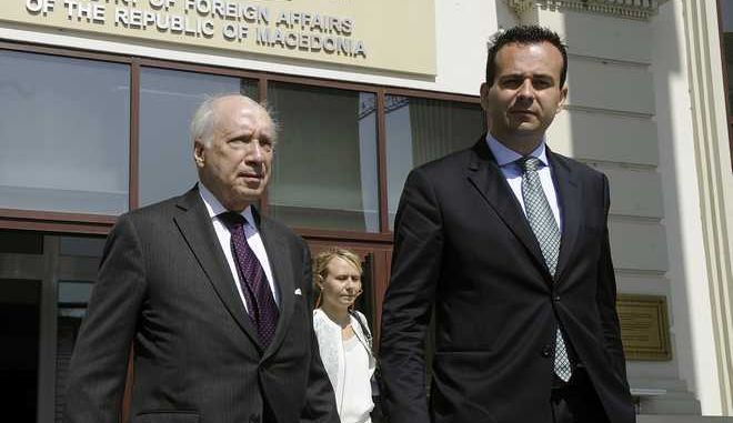 Matthew Nimetz, the United Nations mediator in a name dispute between Macedonia and Greece, left, accompanied by Vasko Naumovski, the new Macedonian appointed negotiator in the talks of the name dispute, right, walks out of the Foreign Ministry building in Skopje, Macedonia, Tuesday, July 29, 2014. Nimetz arrived in Skopje in another try to move Skopje and Athens closer to solving the decade long dispute over the name Macedonia. (AP Photo/Boris Grdanoski)