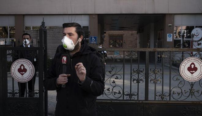 Δημοσιογράφος κάνει ρεπορτάζ έξω από νοσοκομείο.