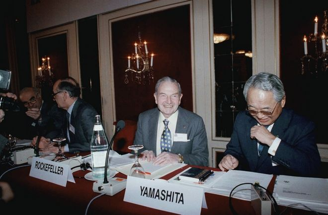Trilateral Commission chairman for North America David Rockefeller, left, and chairman for Japan Isamu Yamashita share a joke before the opening of the 20th meeting of the commission in Paris on Saturday, April 8, 1989. This private commission unites North America, Europe and Japan to bring together individuals from various sectors for focused discussion of common policy problems and proposals for handling them. (AP Photo/Laurent Rebours)