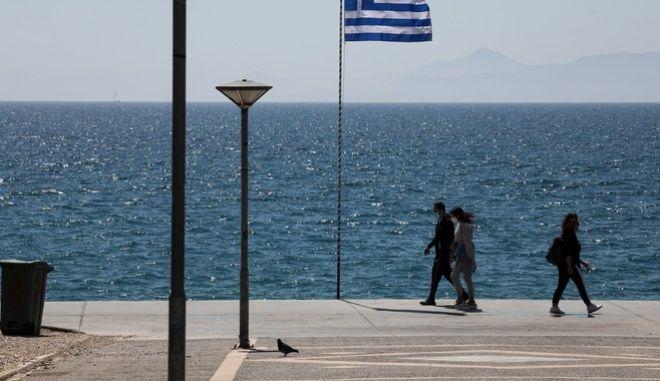 Άνθρωποι με μάσκα περπατάνε στην παραλία Φαλήρου