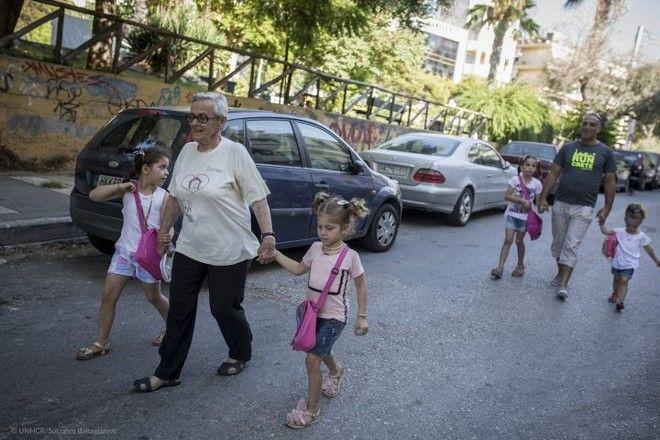 Η ογδονταπεντάχρονη κυρία Κίτσα Βασσιλειάδου, βοηθά τον Malek Bakri να πάει τις κόρες του στο σχολείο στο Ηράκλειο, Κρήτης,