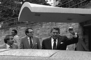U.S. President Ronald Reagan winces and raises his left arm as he was shot by an assailant as he left a Washington hotel, Monday, March 30, 1981, after making a speech to a labor group. The President was shot in the upper left side. (AP Photo/Ron Edmonds)