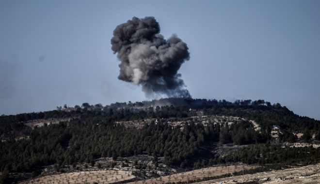 A plume of smoke rises from inside Syria, during Turkish forces bombardment, part of an offensive codenamed Operation Olive Branch, in the Kurdish-controlled enclave of Afrin, Syria, as seen from the border with Syria, in Kilis, Turkey, Sunday, Jan. 28, 2018. Turkish troops and allied Syrian fighters captured a strategic hill in northwestern Syria on Sunday as their offensive to root out Kurdish fighters enters its second week, Turkey's military and Syrian war monitor reported.(Can Erok/DHA-Depo Photos via AP)