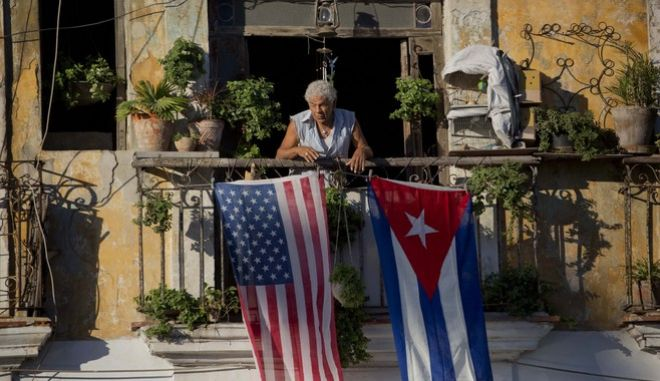 FILE - In this Dec. 19, 2014 file photo, Javier Yanez stands on his balcony decorated with U.S. and Cuban flags in Old Havana, Cuba. On Friday, June 16, 2017, President Donald Trump is expected to turn America's Cuba policy on its second 180-degree spin in three years. Ordinary Cubans are bracing for the worst. (AP Photo/Ramon Espinosa, File)